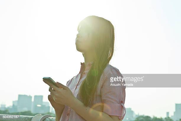 Japanese woman using smartphone at riverside