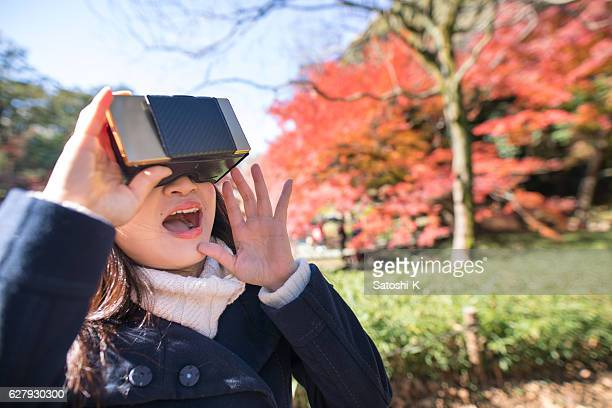 Japanese woman using virtual reality headset in autummn foliage