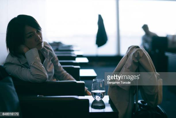 Japanese woman waiting for flight in airport lounge