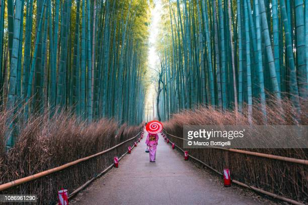 japanese woman walking in bamboo grove, arashiyama, kyoto, japan - kyoto prefecture stock pictures, royalty-free photos & images