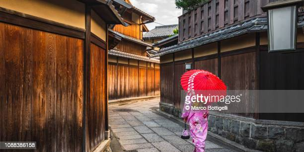 japanese woman walking in the alleys of gion district, kyoto, japan - japan stockfoto's en -beelden