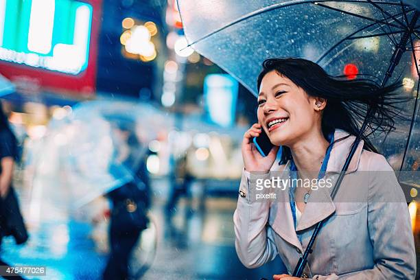 Japanese woman walking in the rain with smart phone