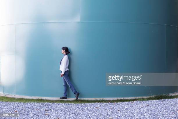 Japanese woman walking near storage tank