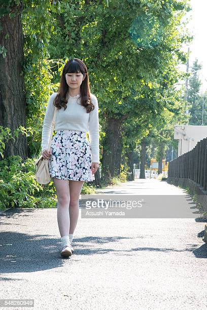 japanese woman walking on street - japanese short skirts stock photos and pictures