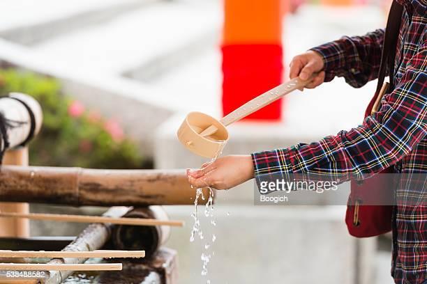 Japanische Frau wäscht Hände beim traditionellen Reinigung Brunnen in-Schrein