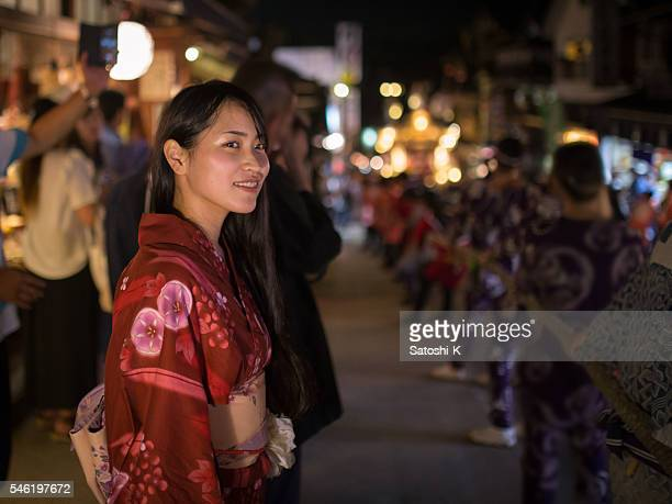 Japanese woman watching night parade of traditional Japanese festival