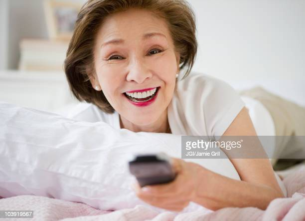 Japanese woman watching television in bed
