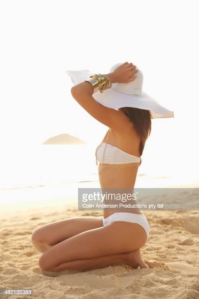 Japanese woman wearing bikini and sun hat on beach