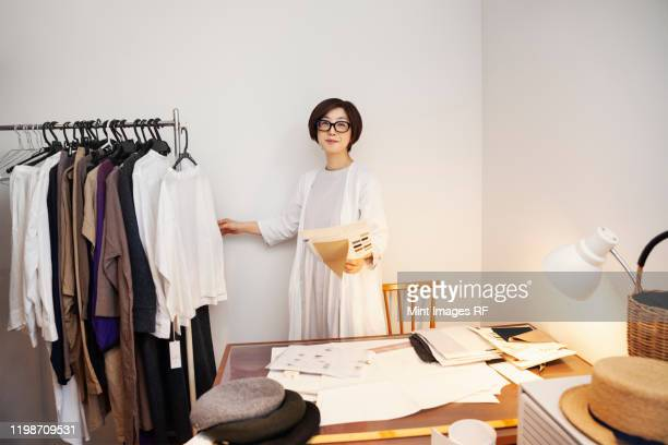 japanese woman wearing glasses working at a desk in a small fashion boutique. - fashion designer stock pictures, royalty-free photos & images