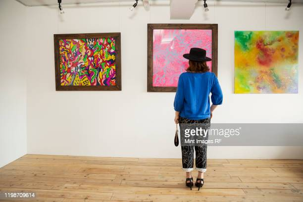 japanese woman wearing hat standing in front of abstract painting in an art gallery. - galleria d'arte foto e immagini stock