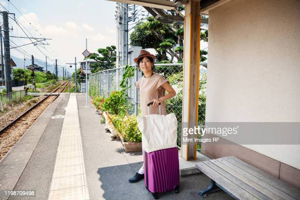 japanese woman wearing hat standing on railway station platform with shopping bag and pink suitcase. - travel ストックフォトと画像
