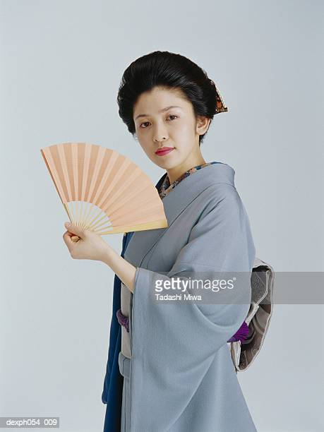 Japanese woman wearing kinomo, holding a paper fan