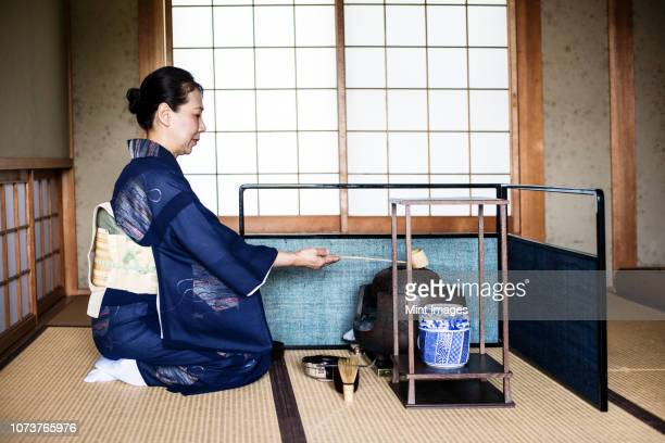 japanese woman wearing traditional bright blue kimono with cream coloured obi kneeling on floor, using a  hishaku, a bamboo ladle, during a tea ceremony. - ceremony stock pictures, royalty-free photos & images