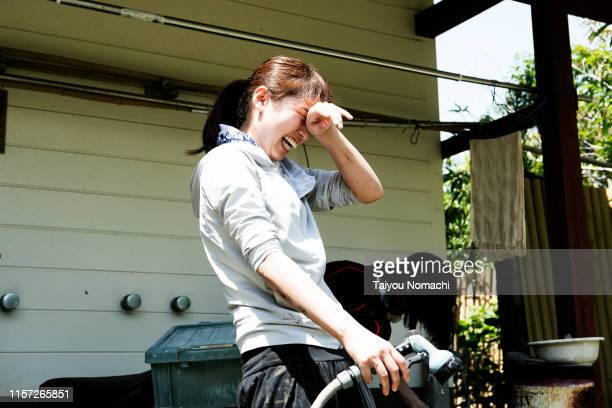 japanese woman who wipes sweat after work is over - attività agricola foto e immagini stock