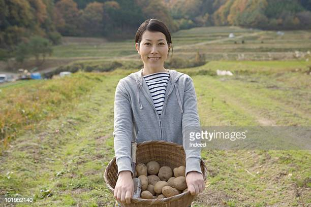 Japanese woman with a basket of potatoes, smiling