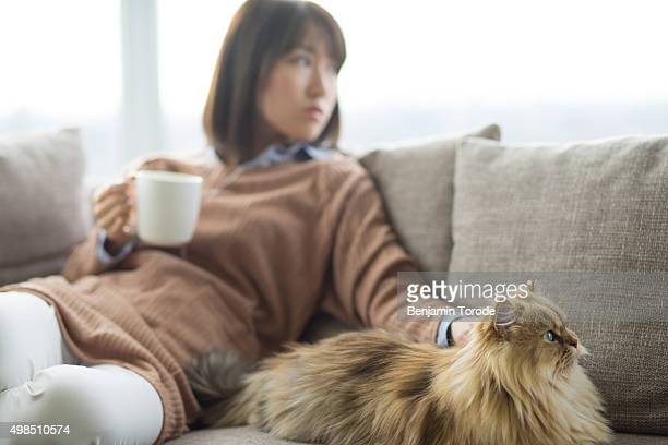 Japanese woman with coffee cup petting cat on sofa