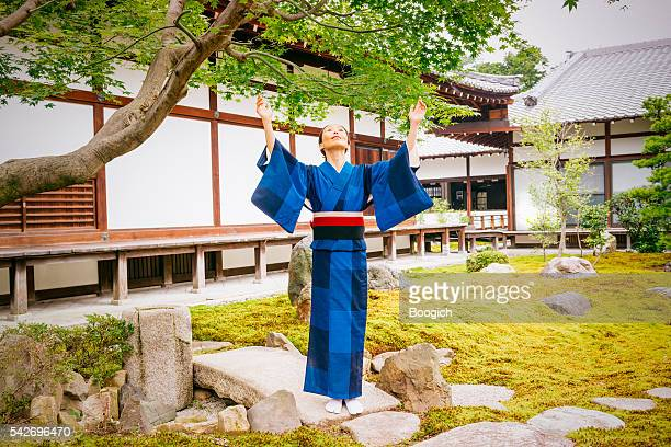 Japanese Woman with Open Arms Looking Up Kyoto Japan Temple