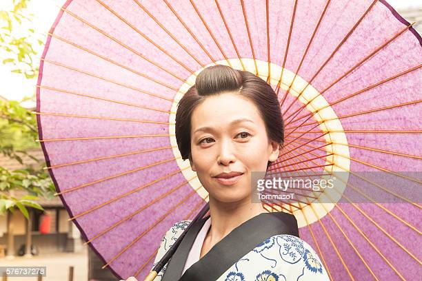 Japanese woman with paper umbrella under the sun