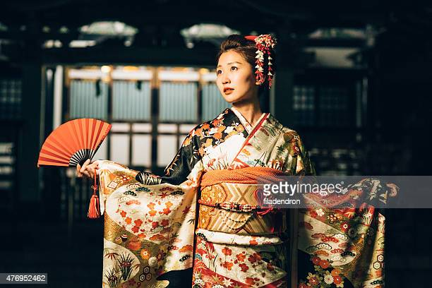 Japanese woman with red hand fan in her hands