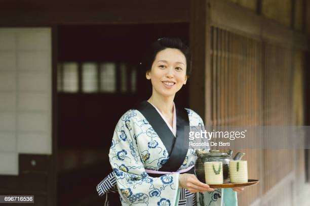 Japanese woman with tea tray outside a traditional japanese house, Edo period