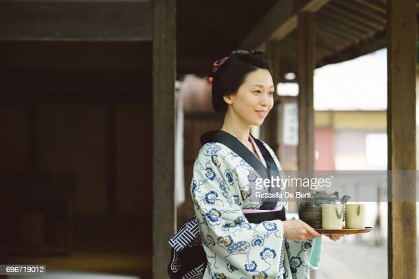 japanese woman with tea tray outside a traditional japanese house, edo period - ceremony stock pictures, royalty-free photos & images