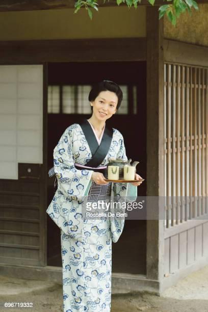 伝統的な日本家屋の外お茶トレイと日本人女性江戸時代 - 宿屋 ストックフォトと画像