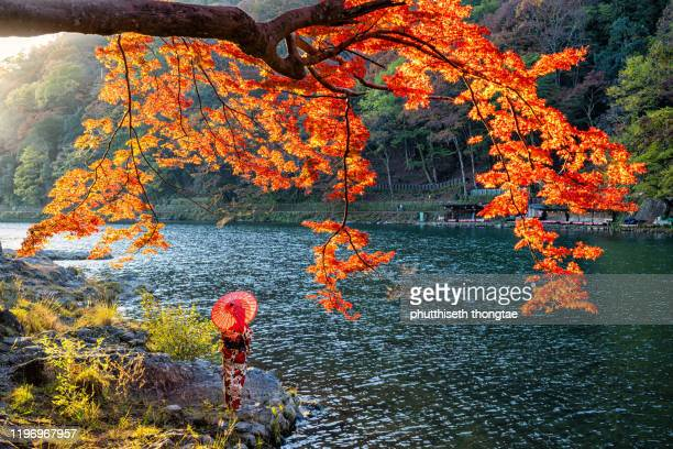 japanese woman with traditional kimono dress and red umbrella at arashiyama, kyoto, japan. - 宇治市 ストックフォトと画像