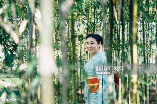 Japanese woman with typical yukata clothes in bamboo forest