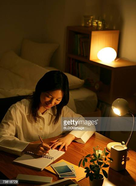Japanese woman writing in bed room in the night