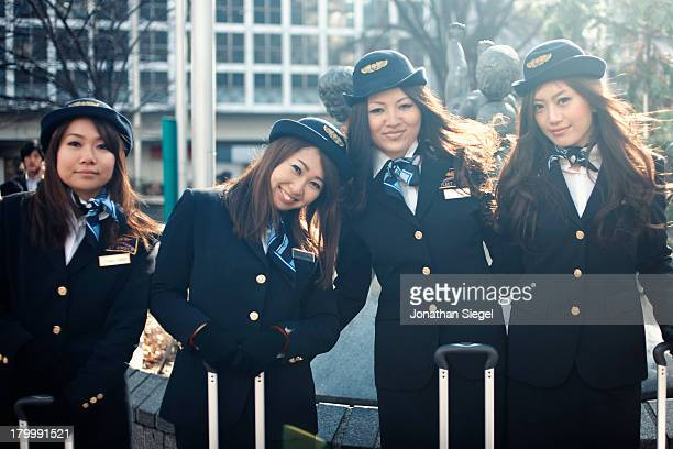 Japanese women dressed as flight attendents walking around Shibuya with their luggage.