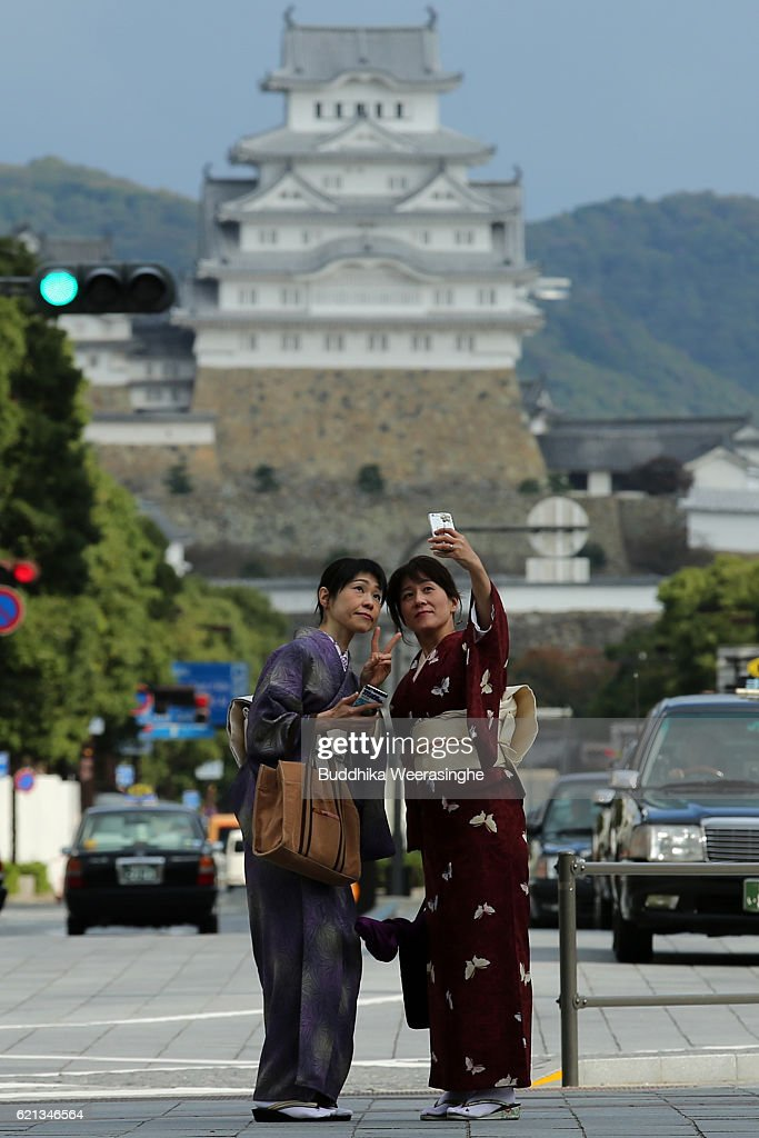 japanese women dressed in colorful traditional costumes called kimono take a picture during the kimono festival - Traditional Castle 2016