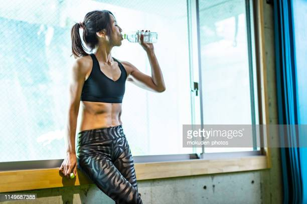 japanische frauen trinkwasser im fitnessstudio - schlank stock-fotos und bilder