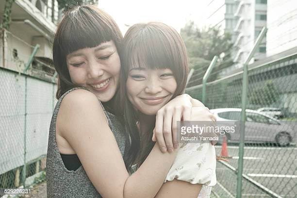 Japanese women hugging on street,smiling