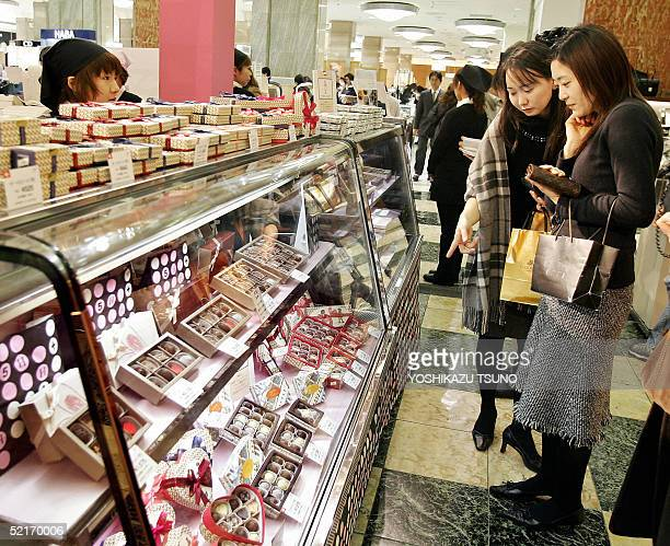 Japanese women look at boxes of chocolates as gifts for St Valentine's Day at Tokyo's Mitsukoshi department store 10 February 2005 Women feel the...