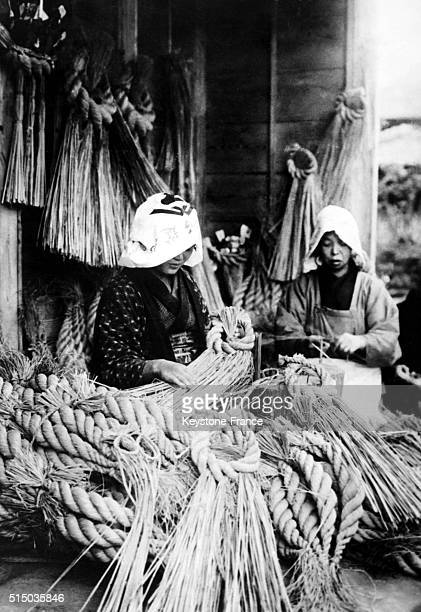 Japanese women making Shimenawa decorations for the front door on new year's eve in Japan on January 27 1919