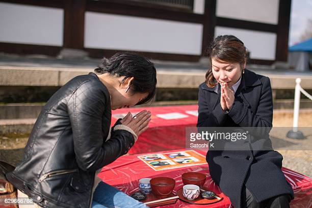 Japanese women praying before eating Japanese food in temple