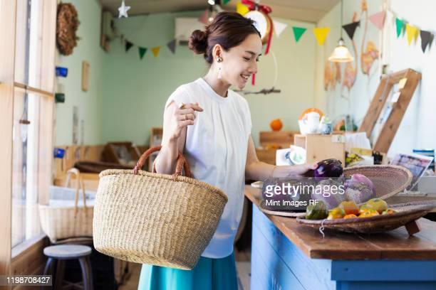 japanese women shopping fresh vegetables in a farm shop. - 女性 ストックフォトと画像