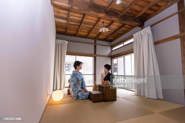 旅館の日本部屋に座っている日本人女性 - 日本建築 ストックフォトと画像