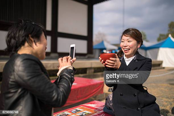 Japanese women taking pictures of red bean soup in temple
