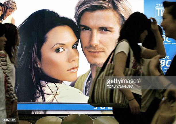 Japanese women walk past an advertizing poster for a beautytreatment clinic chain showing English soccer superstar David Beckham and his wife...