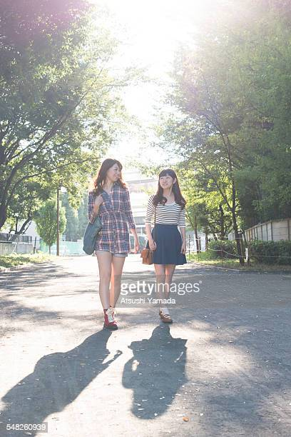 japanese women walking in park,smiling - japanese short skirts stock photos and pictures