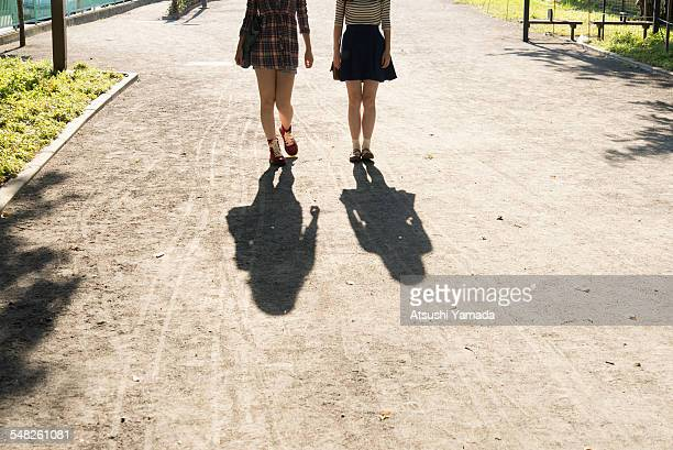 japanese women walking on street,rear view - minirok stockfoto's en -beelden