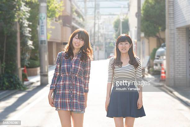 japanese women walking on street,smiling - japanese short skirts stock photos and pictures