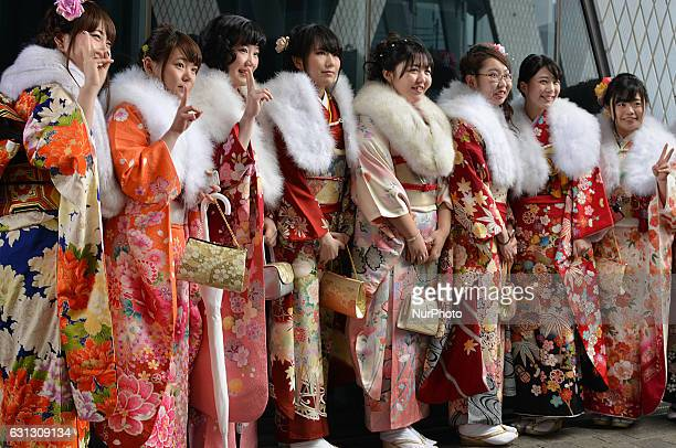 Japanese women wearing kimonos pose for pictures as they attend a Coming of Age Day celebration ceremony at an amusement park in Tokyo January 9,...
