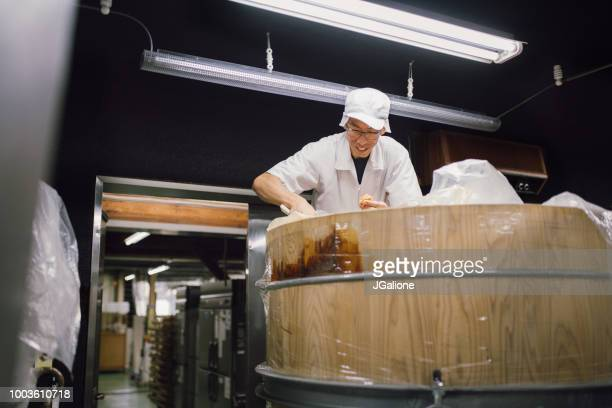 Japanese worker inspecting miso