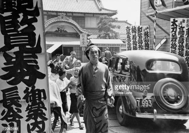 A Japanese wrestler approaches the entrance of the sumo wrestling stadium in Ryogoku Tokyo circa 1955