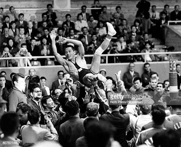 Japanese wrestler Yojiro Uetake is lifted up by fellow team members after finishing in first place in the final round to win the gold medal in the...