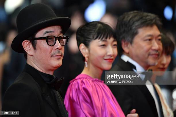 Japanese writer and actor Lily Franky poses with Japanese actress Sakura Ando and Japanese director Hirokazu KoreEda as they arrive on May 13 2018...