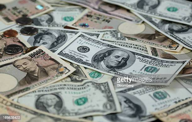 Japanese yen and US dollar banknotes along with coins of various denominations are arranged for a photograph in Tokyo Japan on Friday May 31 2013...