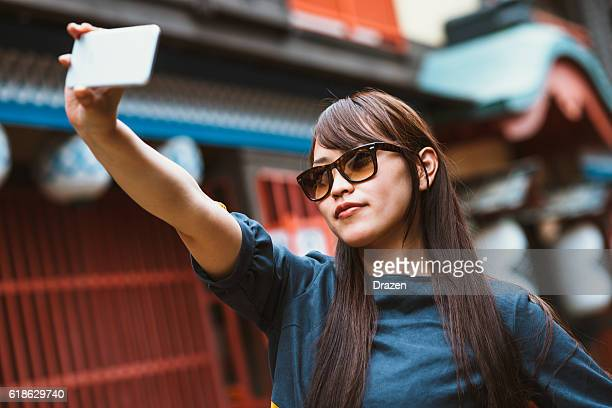 Japanese young beautiful woman taking selfie for social media feed